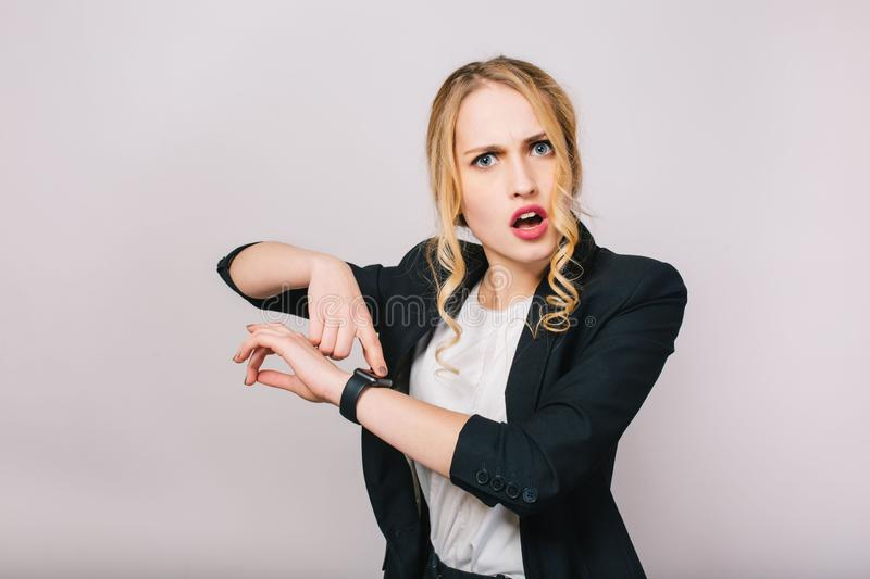 Busy office work time of astonished young blonde woman in white shirt and black jacket looking at camera isolated on. White background. Meeting, watch, being royalty free stock photos