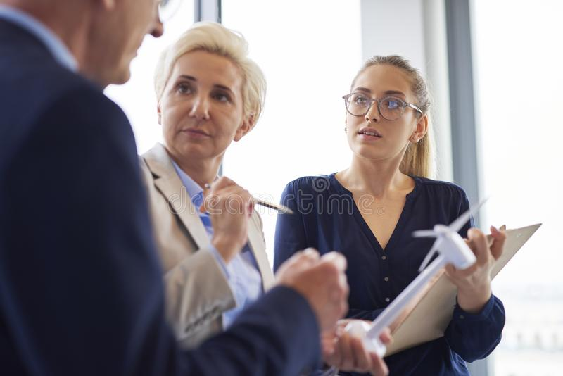 Busy office workers having a conversation in the office stock image