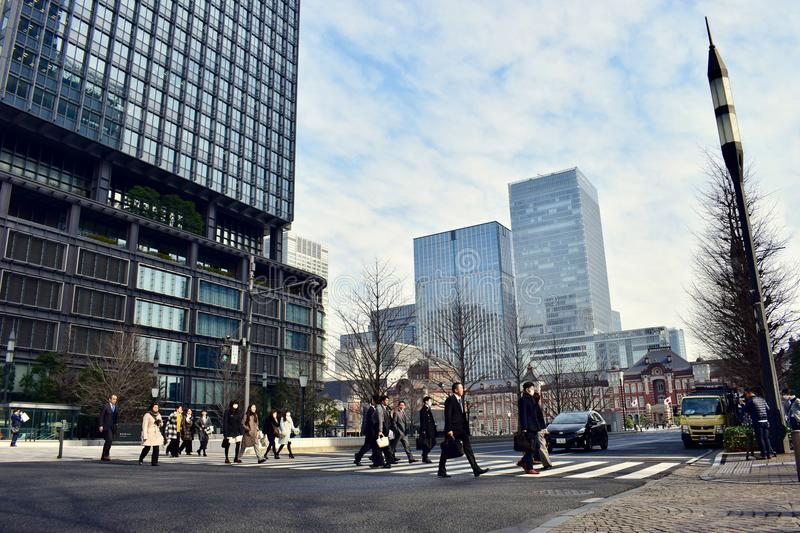 Busy people walk around modern office Buildings in Tokyo Japan. People walk across the street around tall office buildings in the business finance center with royalty free stock image
