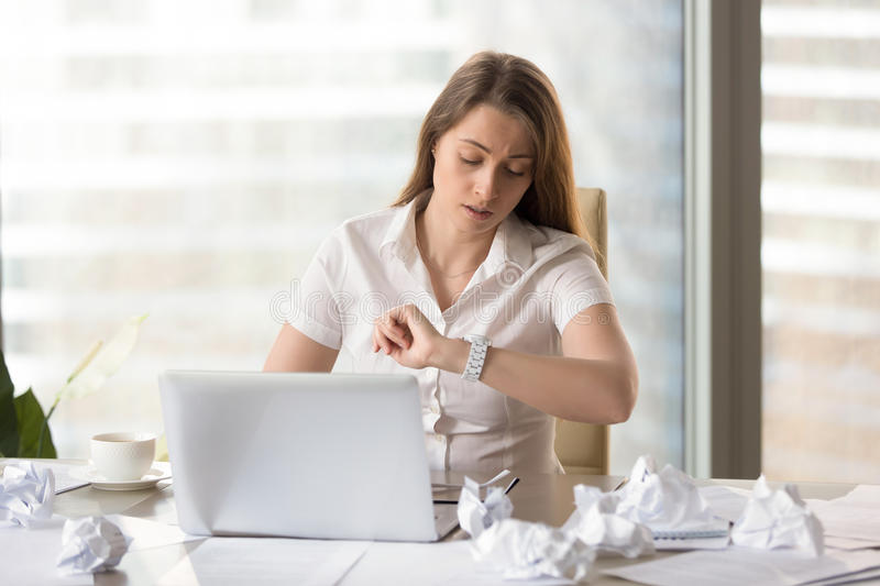 Busy punctual businesswoman checking time to deadline, looking a. T wristwatch while working with laptop and documents, need to finish work on time, counting on stock photo