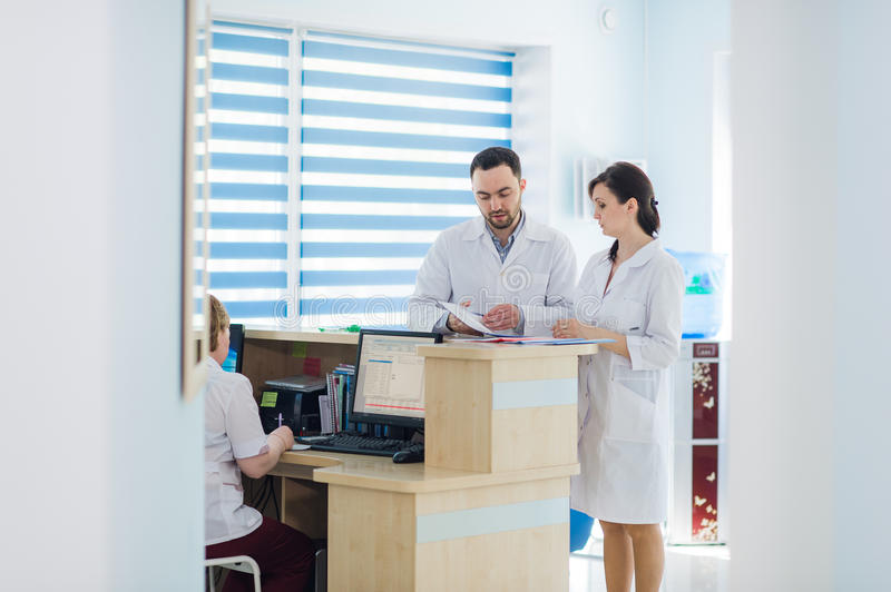 Busy reception in a hospital with doctors and receptionists.  stock image