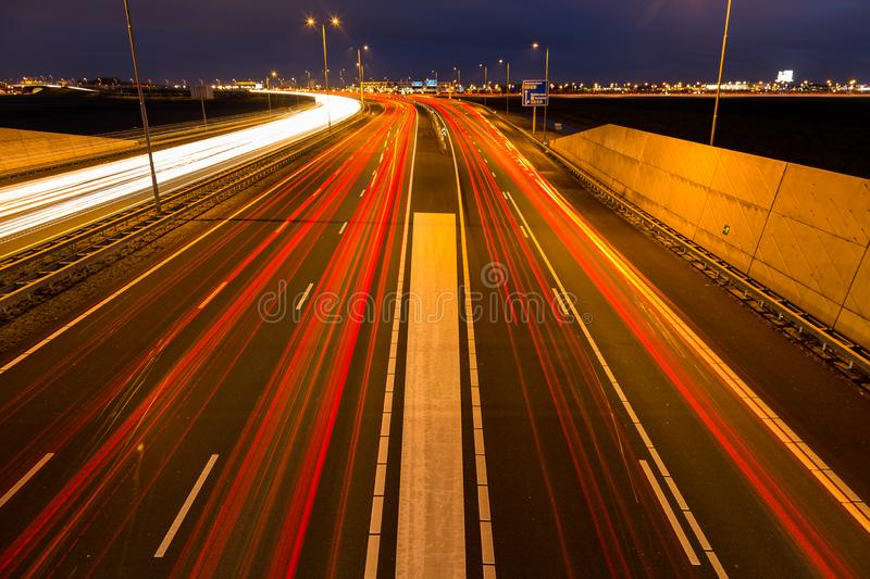 Busy rush hour traffic leaves light trails on the A9 highway. Busy rush hour traffic leaves red light trails on the A9 highway near Amsterdam, Schiphol to royalty free stock photos