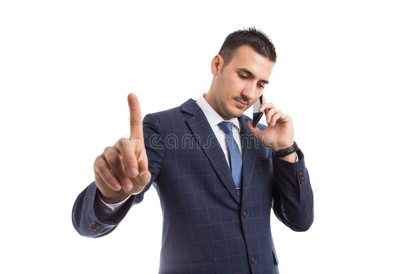 Busy salesman taking a call. On smartphone and making index finger hold gesture as important business concept isolated on white background royalty free stock photos