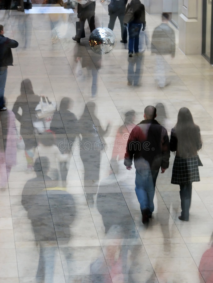 Busy shoppers. Crowd of shoppers in shopping mall. Two images overlaid to give ghosting effect stock photo