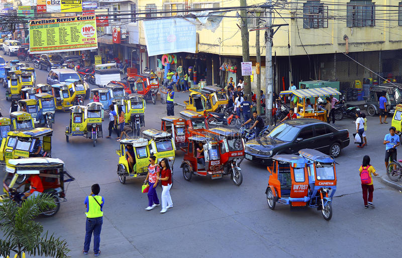 Busy street scene : tuguegarao city, philippines. Commuters and common transport tricycles in motion during busy hours at tuguegarao city in the philippines stock photography
