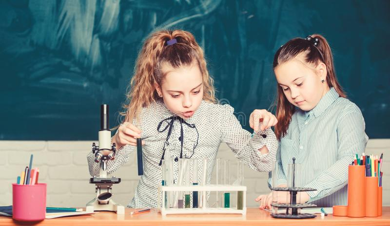 Really busy. students doing biology experiments with microscope. Little children at laboratory. Little kids learning stock photo