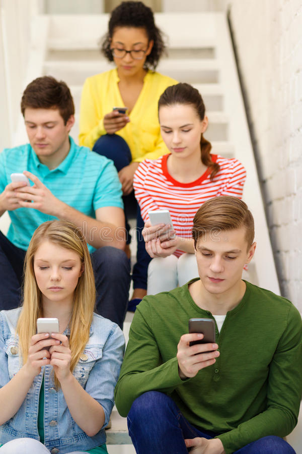 Busy students with smartphones sitting on stairs stock photography