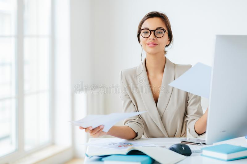 Busy successful female manager works with papers in office, poses at desktop, wears spectacles and formal outfit, busy preparing. Report, looks confidently at royalty free stock photos