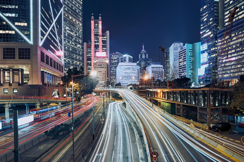 Busy traffic in modern city. Light trails of cars against night urban skyline, Hong Kong royalty free stock image