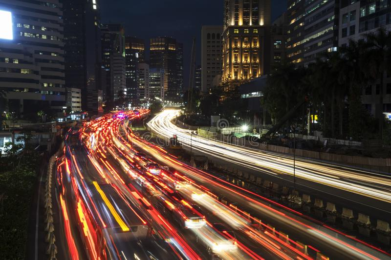 Busy traffic with trail lights in Jakarta city. Top view of busy traffic with trail lights on the highway at night time in Jakarta city royalty free stock photography