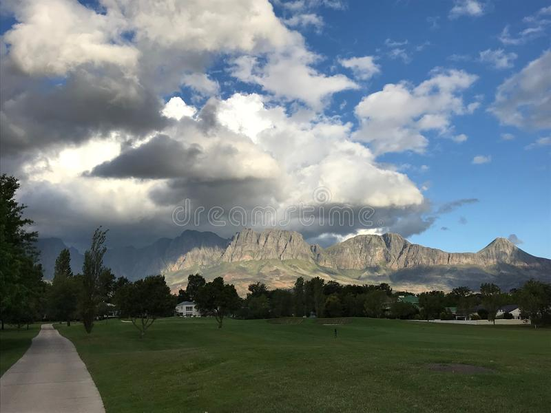 Busy weather in Erinvale. View of the Hottentots Mountains from Erinvale Golf Course. This is taken from the 3rd fairway. It was on a blowy, rainy, sunny royalty free stock photo