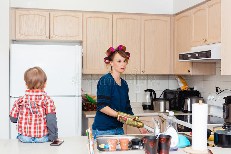 Busy white Caucasian young woman mother housewife with hair-curlers in her hair cooking preparing dinner meal in kitchen royalty free stock photography