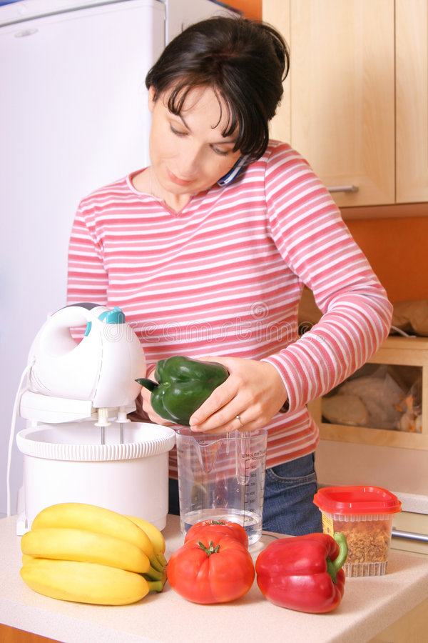 Busy Wife. A woman preparing food and talking on the phone stock images