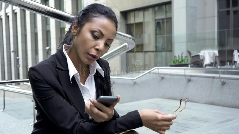 Busy woman checking e-mails on smartphone outdoors near office, lunch time stock photos