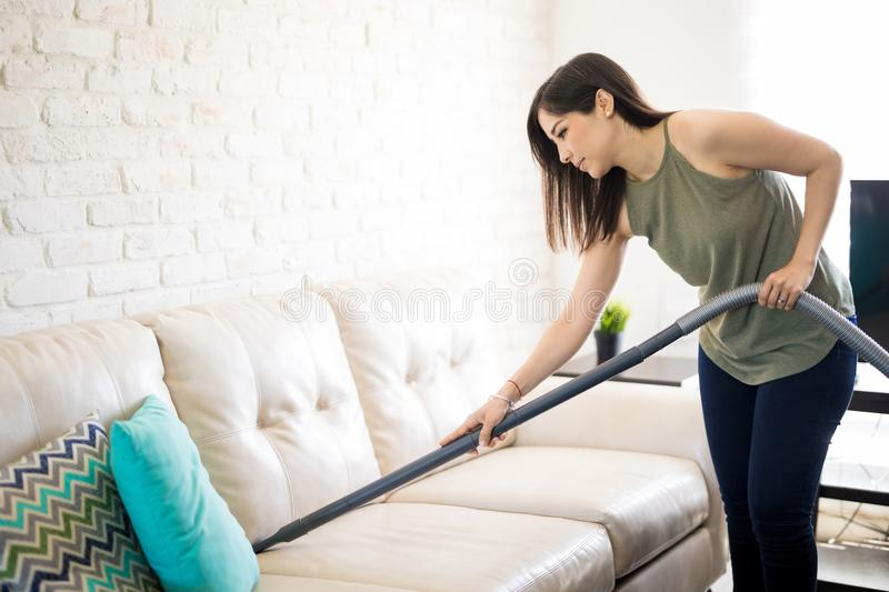 Busy woman cleaning sofa with vacuum cleaner royalty free stock photos