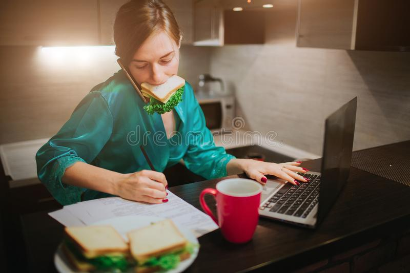 Busy woman eating, drinking coffee, talking on the phone, working on a laptop at the same time. Businesswoman doing stock photography