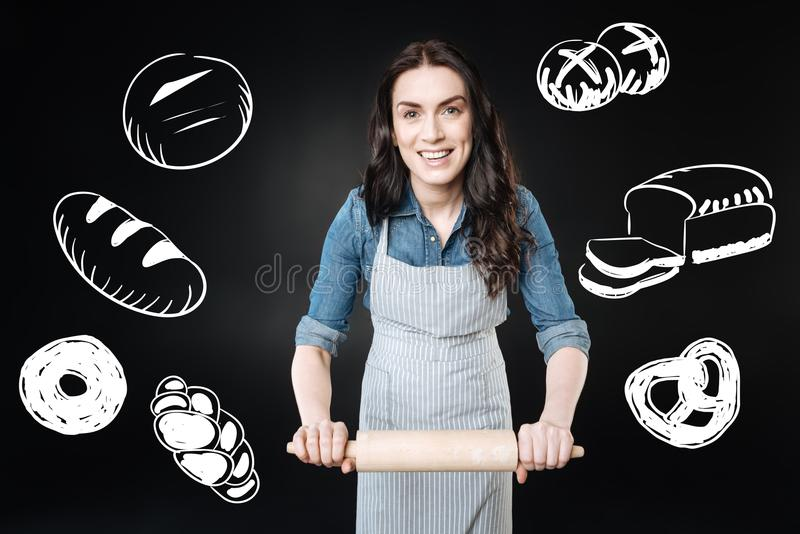 Positive woman holding a rolling pin while learning to cook bread stock images