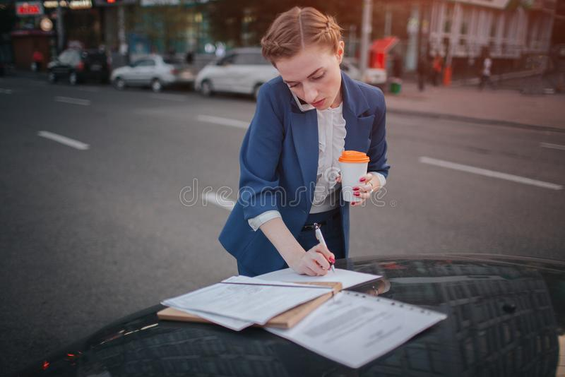 Busy woman is in a hurry, she does not have time, she is going to talk on the phone on the go. Businesswoman doing royalty free stock image