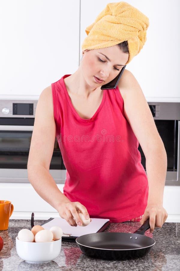 Busy woman making scrambled eggs royalty free stock photos