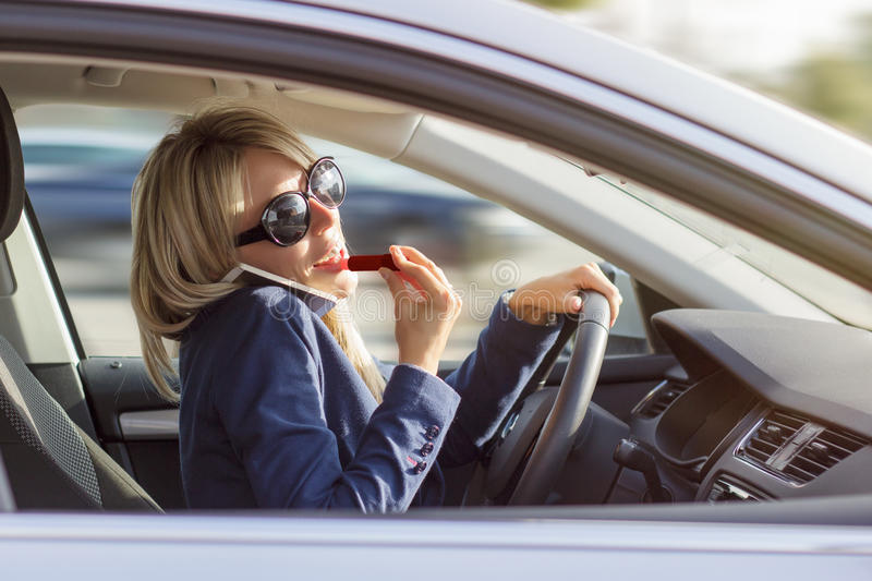 Busy woman manage to talk on phone and do makeup. While driving a car royalty free stock photo