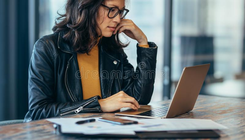 Busy woman sitting on desk and working on laptop royalty free stock photography
