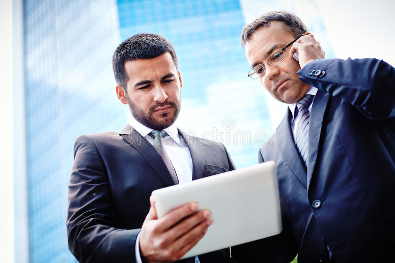 Busy working. White-collar workers discussing business project in touchpad and consulting via mobile phone stock photo
