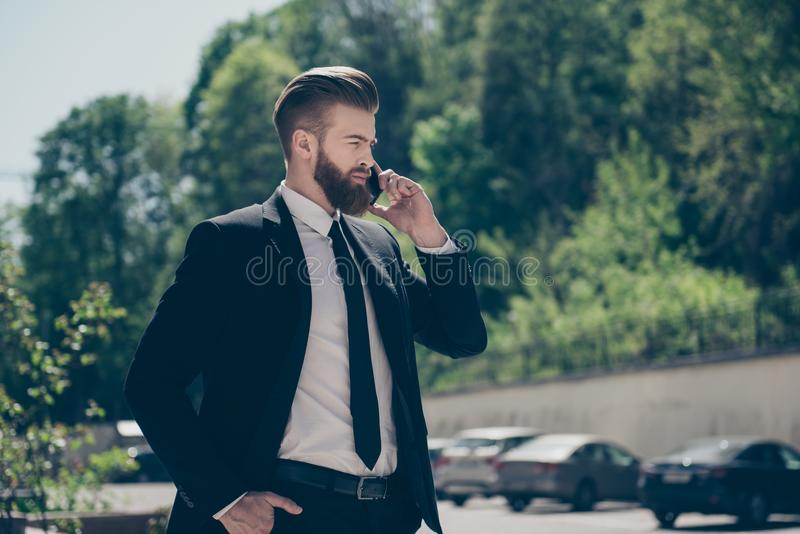 Busy young authoritative red bearded stylish man in formalwear. Talking on mobile phone on the street on sunny weather stock images