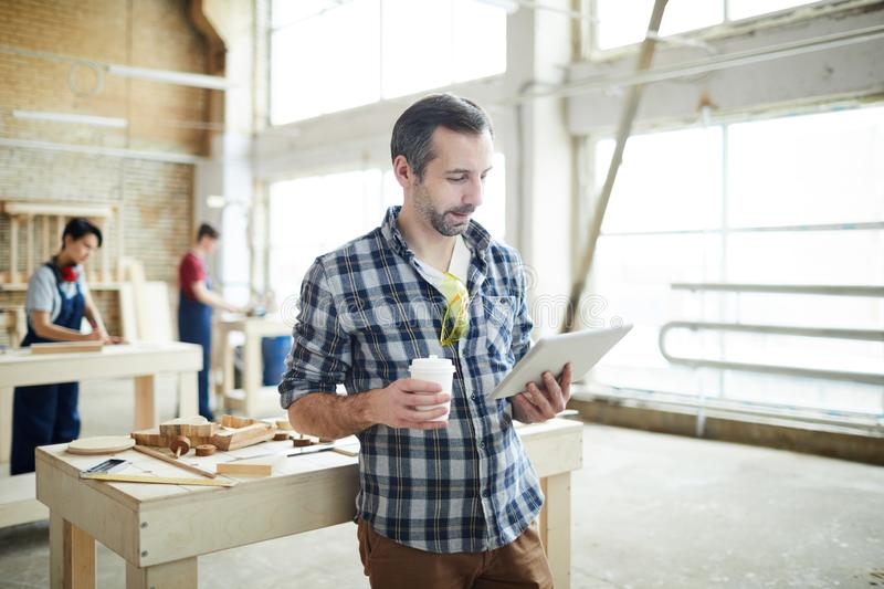 Busy young joiner reading article on tablet. Busy pensive young joiner with safety goggles on tshirt leaning on table with wooden details and tools and drinking royalty free stock images