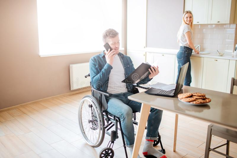Busy young student on wheelchair studying and taking on phone. Guy with special needs and disability. Holding opened stock photo