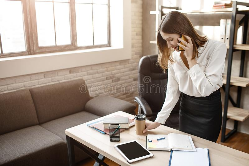 Busy young woman stantd at table in room. She talk on phone and write in notebook. royalty free stock photos