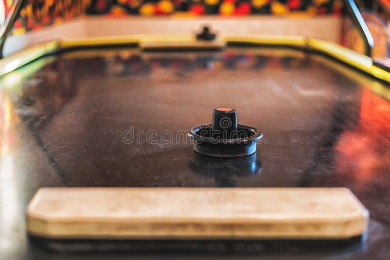 Butée noire sur le Tableau gris d'hockey d'air avec le galet et le flipper bleus de Bokeh et jeux à l'arrière-plan dans l'arcade photos stock