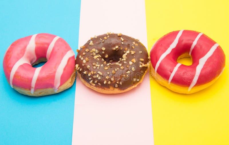 Butées toriques assorties avec du chocolat sur le fond coloré photographie stock libre de droits