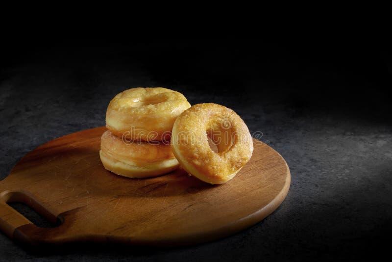 Butées toriques avec du sucre d'un plat en bois au-dessus d'un fond foncé de table image libre de droits