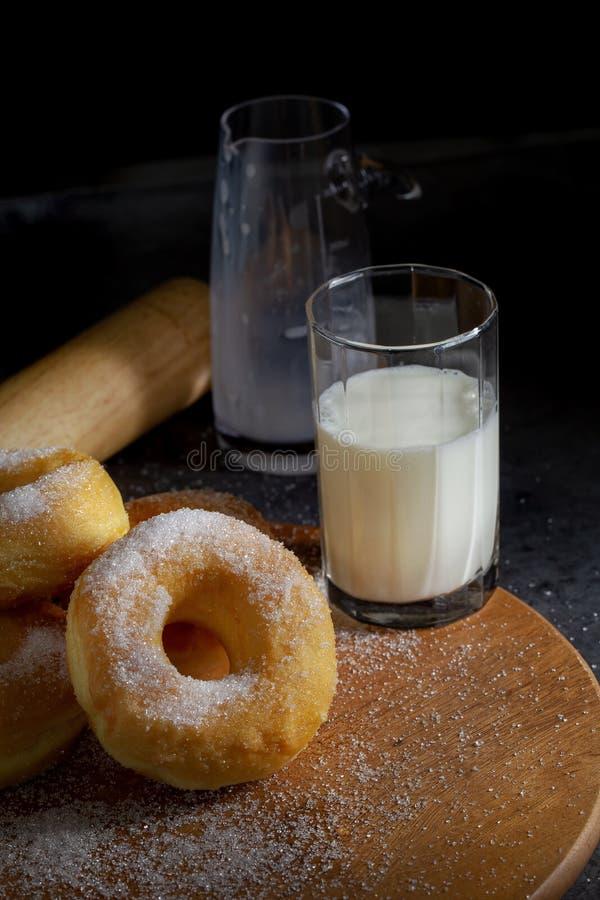Butées toriques avec du sucre d'un plat en bois au-dessus d'un fond foncé de table photographie stock