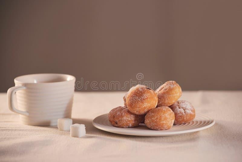Butées toriques avec du sucre sur la tasse de plat et de café sur le fond blanc photos stock