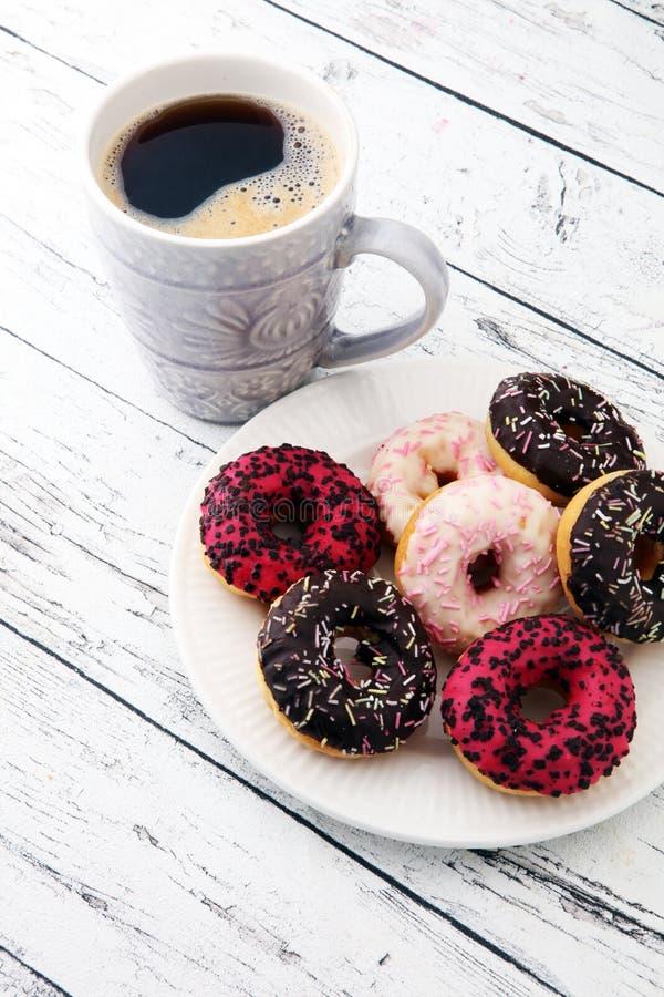 Butées toriques et café pour un petit déjeuner doux sur le fond en bois images stock