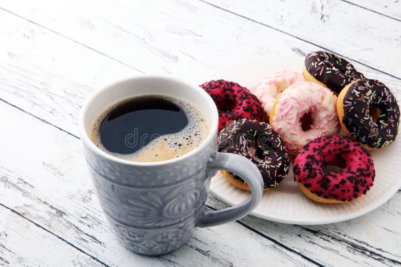 Butées toriques et café pour un petit déjeuner doux sur le fond en bois photographie stock
