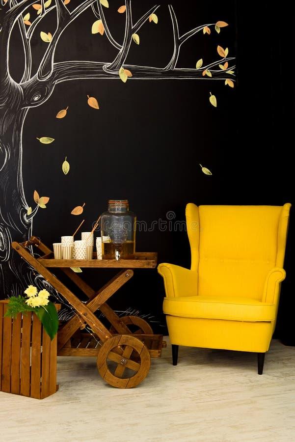 Butaca amarilla brillante al lado del carro de madera fotografía de archivo