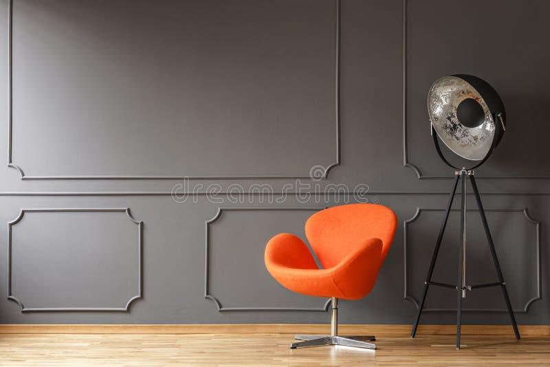 Butaca anaranjada al lado de la lámpara en ingenio mínimo del interior de la sala de estar imagen de archivo libre de regalías
