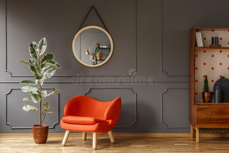 Butaca anaranjada brillante, un gabinete de madera retro y un espejo en a imagen de archivo libre de regalías