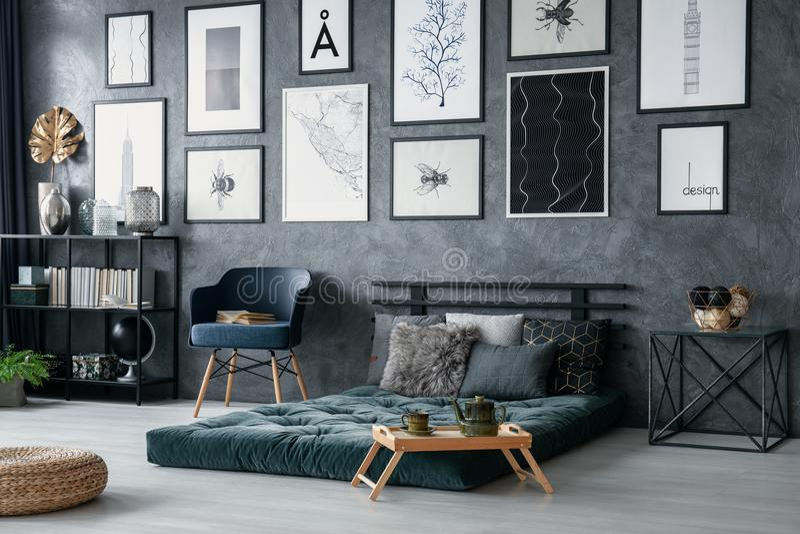 Butaca azul al lado del futon verde en interior del dormitorio con el taburete y la galería de carteles Foto verdadera foto de archivo