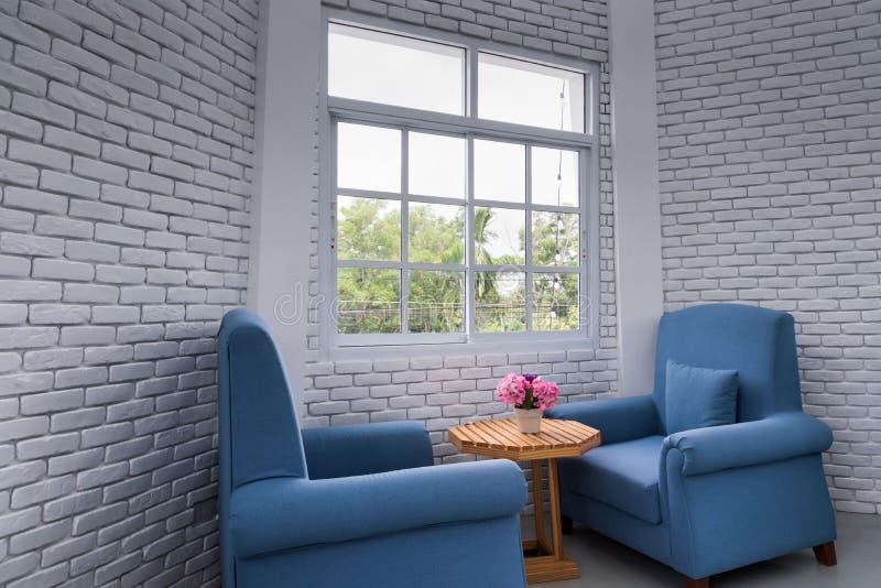 Butaca clásica azul en sala de estar moderna del desván con bric blanco imágenes de archivo libres de regalías