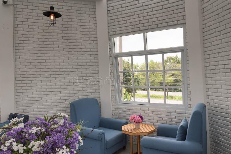 Butaca clásica azul en sala de estar moderna del desván con bric blanco fotografía de archivo libre de regalías