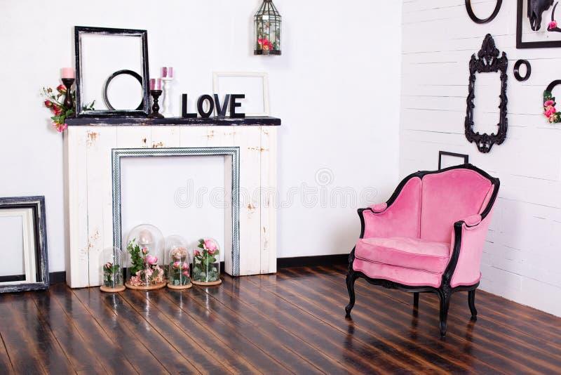 Butaca del velor del vintage, en un cuarto brillante y una chimenea artificial Ático interior con las paredes blancas de madera M fotos de archivo