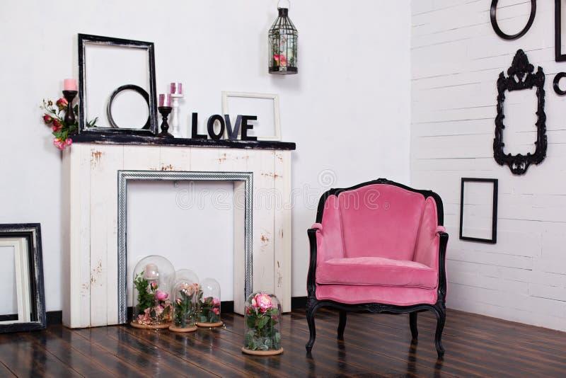 Butaca del velor del vintage, en un cuarto brillante y una chimenea artificial ?tico interior con las paredes blancas de madera M fotografía de archivo libre de regalías