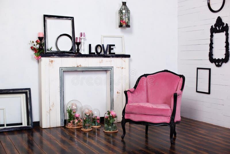 Butaca del velor del vintage, en un cuarto brillante y una chimenea artificial ?tico interior con las paredes blancas de madera M imagen de archivo libre de regalías