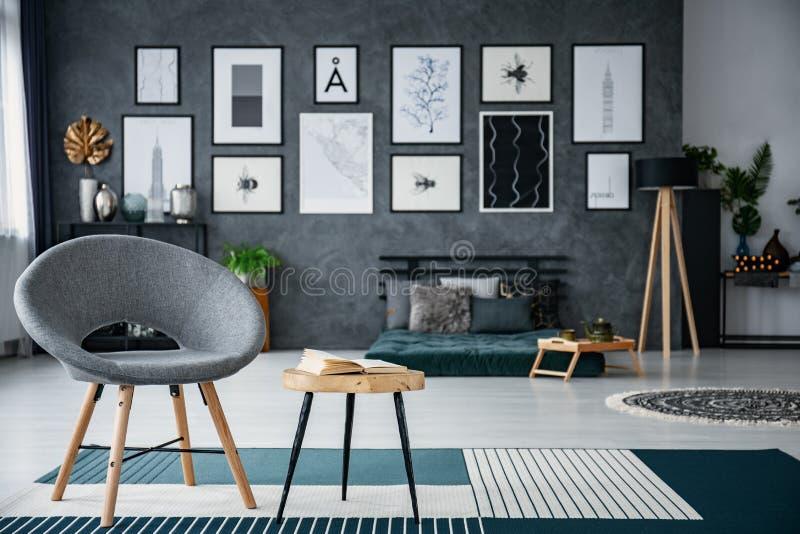Butaca gris al lado de la tabla en la alfombra en interior de la sala de estar con la galería de carteles Foto real con el fondo  fotos de archivo