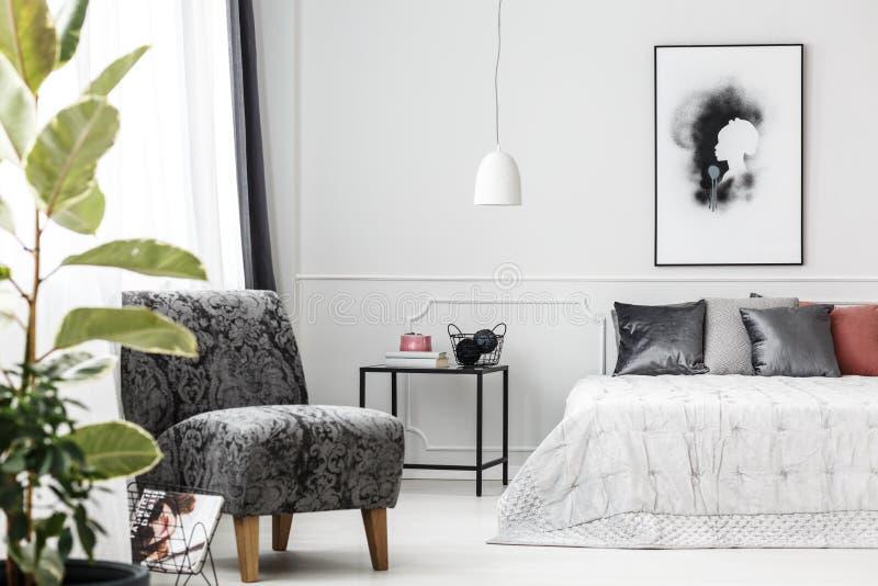 Butaca gris en dormitorio fotografía de archivo libre de regalías