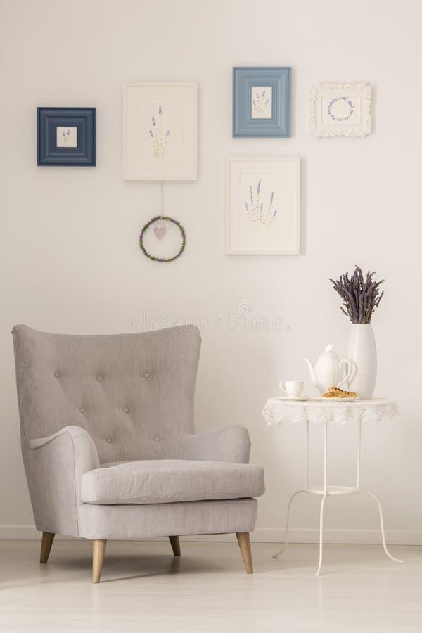 Butaca gris que se coloca al lado de la mesa lateral del metal con el jarro y taza de té, galletas francesas y lavanda fresca en  imagen de archivo