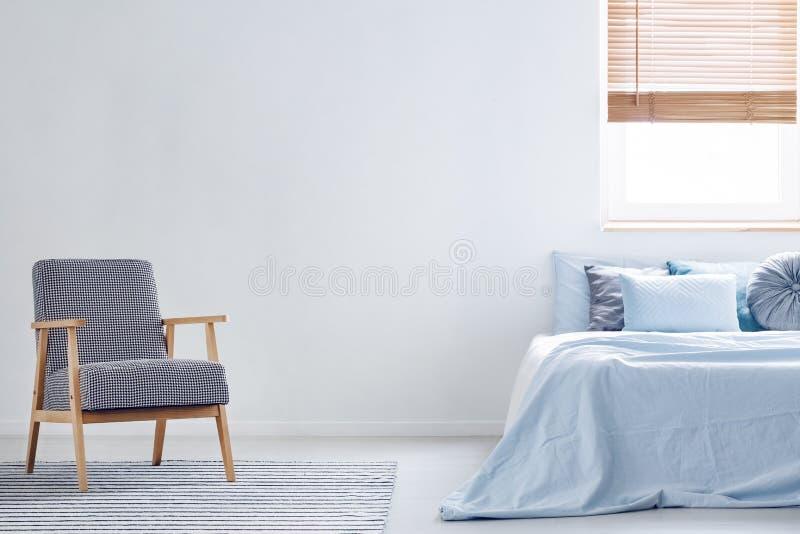 Butaca modelada en la alfombra en interior mínimo del dormitorio con el bl foto de archivo